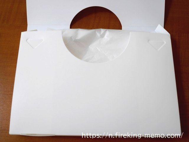 ケースの支え板を挟む形でゴミ袋をたたみ、収納する