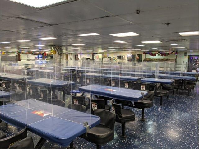 """为防控疫情,""""埃塞克斯""""号餐厅内的桌子上都设置了隔板"""