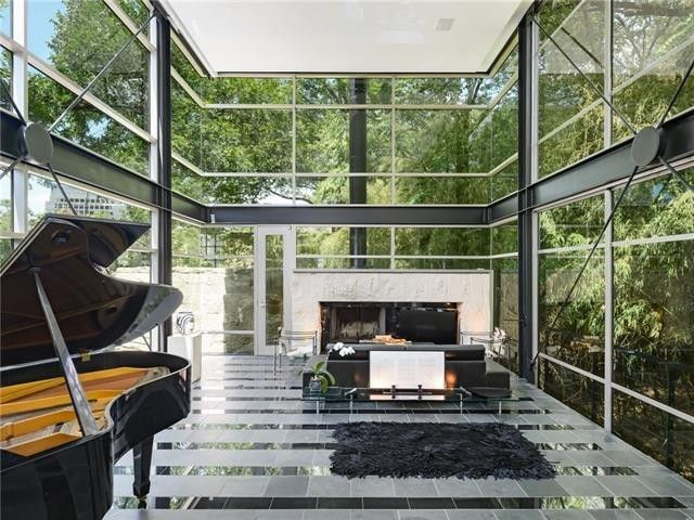 Stone fireplace set into a wall of glass