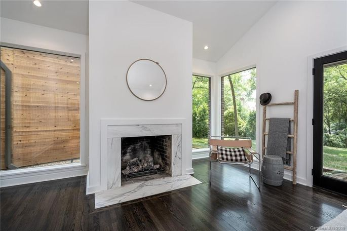 Fresh hardwood and a marble fireplace surround modernize the master bedroom.