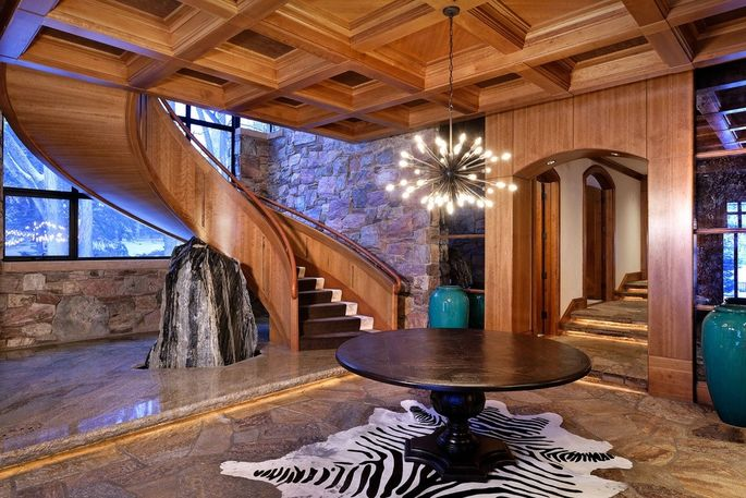 Floating wood staircase with rock jutting from the floor