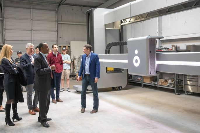 Ben Carson, secretary of the Department of Housing and Urban Development, foreground, toured the company's factory last week, meeting with Icon co-founder Jason Ballard, in blue jacket.