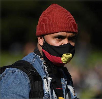 image of Aboriginal man wearing face mask with Aboriginal flag