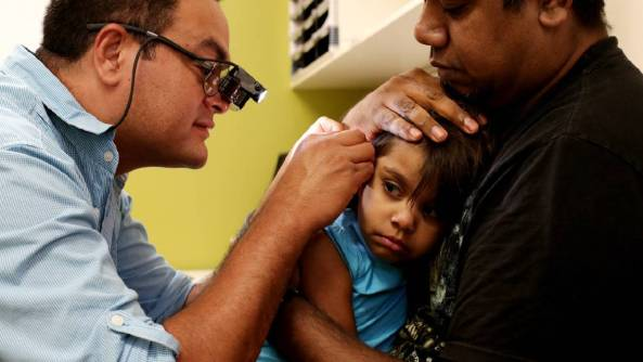 medical professional checking a toddler's ear, toddler is being held by parent or carer