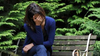 Aboriginal woman sitting on wooden bench in garden, head in hands