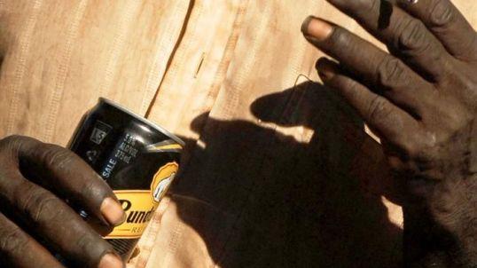 Aboriginal hands holding can of Bundaberg Rum & cigarette