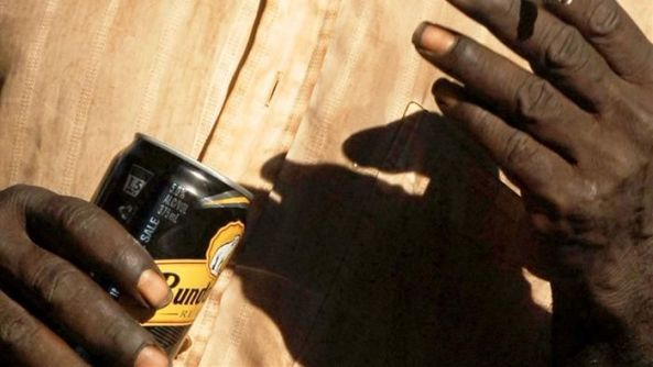 Aboriginal hands holding can of Bundaberg Rum & cigarette