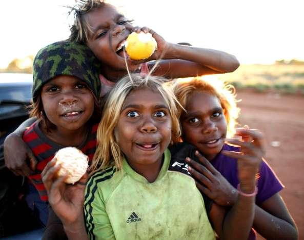 four Aboriginal children with oranges