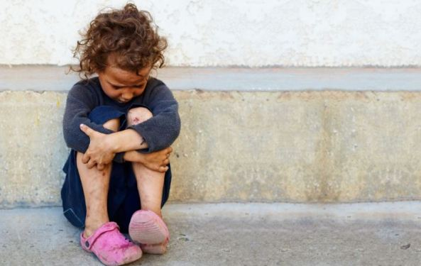small Aboriginal child with tangled hair, scrapped knees sitting on concrete floor with head in knees, hands wrapped around legs