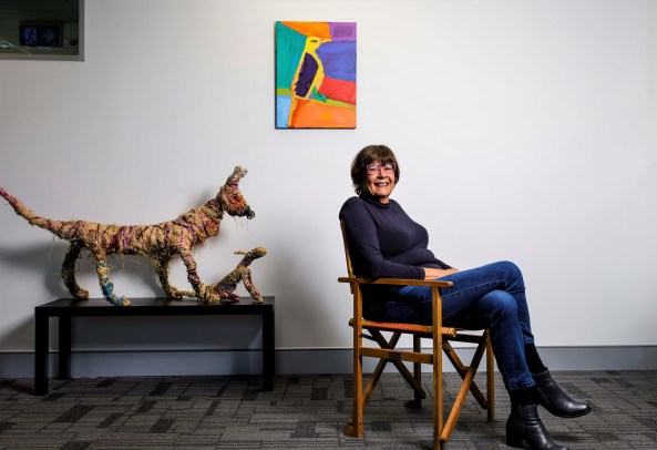 NACCHO CEO Pat Turne sitting in a chair smiling with woven dog sculptures on a small table behind her & an a colourful Aboriginal painting of a bird