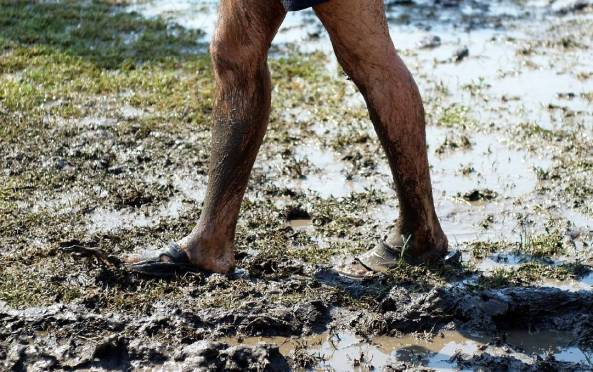 muddy legs with rubber sandals walking across muddy grassy wet ground