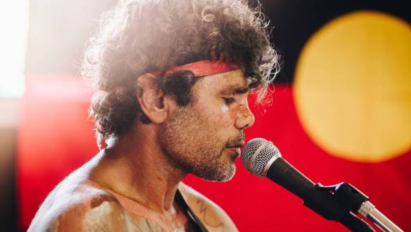 Aboriginal man from Bowraville Richie Jarrett singing into microphone, Aboriginal flag as backdrop