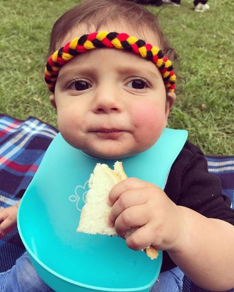 toddler Archie eating sandwich blue plastic bib and Aboriginal colours headband