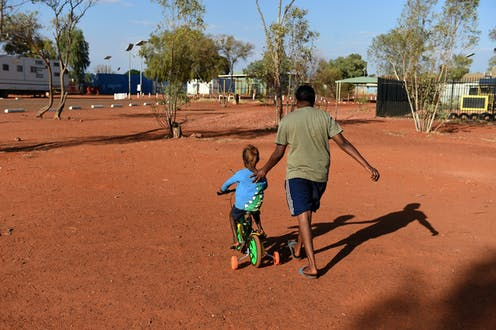 Aboriginal man pushing young Aboriginal child on a tricycle in desert community