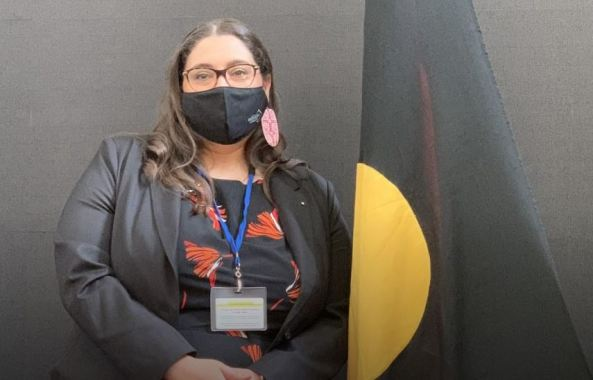 Sheena Watt with mask standing next to Aboriginal flag on stand