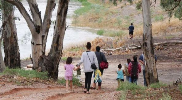 photo of 1 Aboriginal man, 3 Aboriginal women & 4 Aboriginal children walking along river