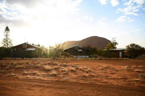 remote community buildings with Uluru in background