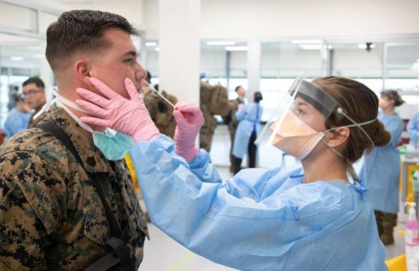 US marine in uniform being tested by health professional in PPE