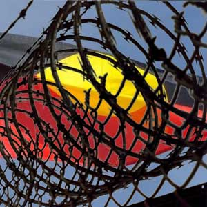 rings of razer wire fence with Aboriginal flag flying in the background