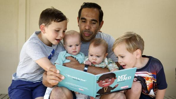 Adelaide Crows star Eddie Betts reading his book My Kind to twin babies & two young boys