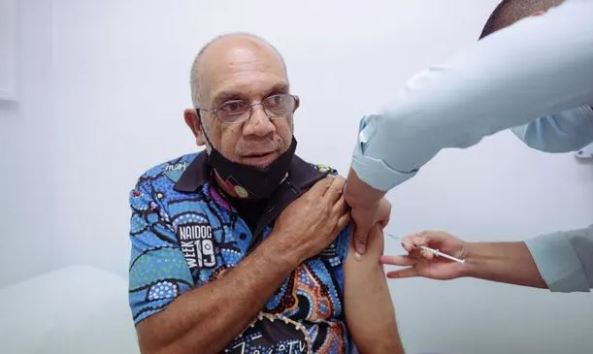 photo of Cecil Phillips, 63, receiving AstaZeneca vaccine by registered nurse, Sam Parimalanathan at AMS Redfern