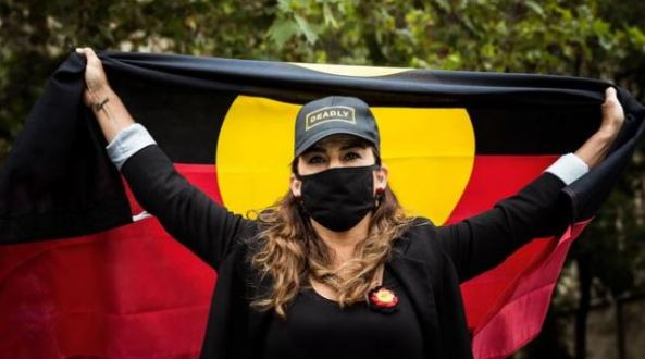 Indigenous Senator Lidia Thorpe holding Aboriginal flag & wearing hat with the word Deadly at an Invasion Day rally in January 2021