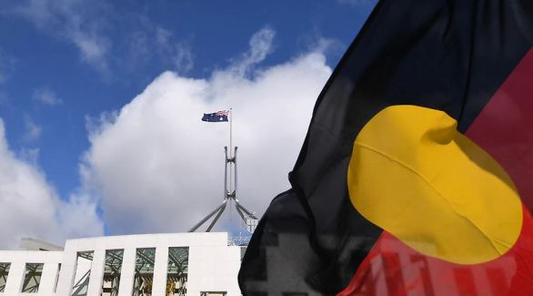 an Aboriginal flag flies outside Parliament House in Canberra