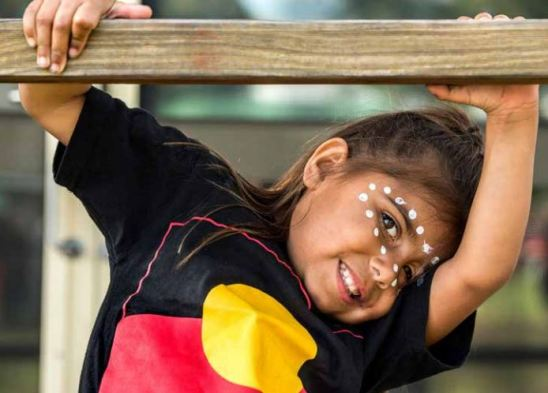 young Aboriginal girl Allorah Saunders with face paint, wearing t-shirt with Aboriginal flag, hanging from a bar, head half concealed by her arm
