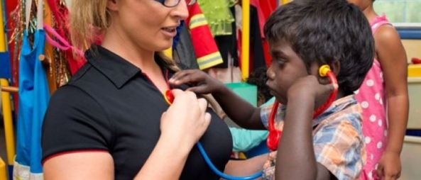 small Aboriginal boy pretending to listen to heart of adult woman with Aboriginal girl & rack of dress-ups in the background