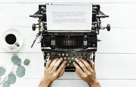 hands on keyboard of 1920s typewriter, white painted wooden surface