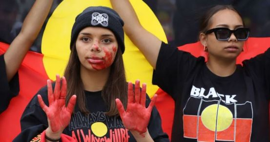 2 young Aboriginal women BLM protestors, one with t-shirt Always Was Always Will Be holding up hands covered in red paint to indicate blood, other woman holding Aboriginal flag behind her with raised arms, t-shirt with text black' and Aboriginal flag broken into 4 horizontal rectangular segments