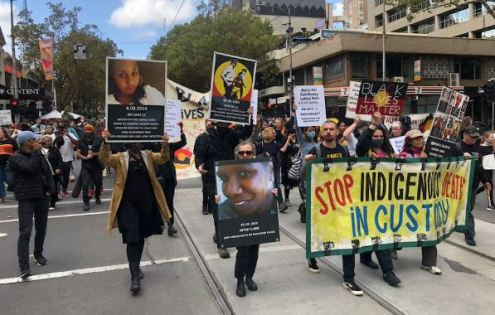 End Black Deaths In Dustody rally in Naarm Melbourne to mark 30th anniversary of the Roayl Commission into Aboriginal Deaths in Custody - crowd carrying photos, signs, placards