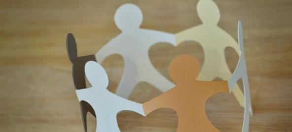 six paper dolls, 3 white, one dark brown, one tan hands joined in acircle on wooden surface