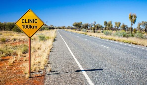 outback road with yellow road sign with words CLINIC100km