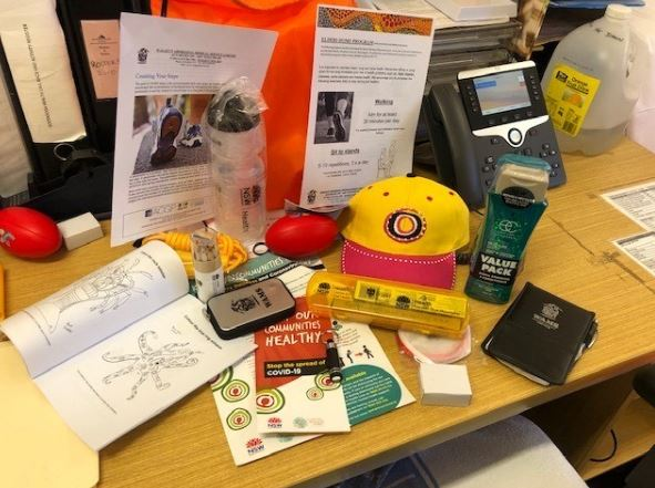 desk with contents of a WAMS cCOVID-19 are package, information brochures, hat, shampoo, colouring books, stress balls, water bottle, rope