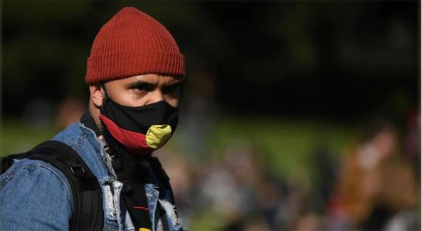 blurred background of green hill & people, clear image Aboriginal man with Aboriginal flag mask, ochre beanie, denim jacket, strap of black backpack looking serious