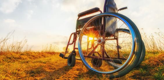 wheelchair sitting in a field at sunset