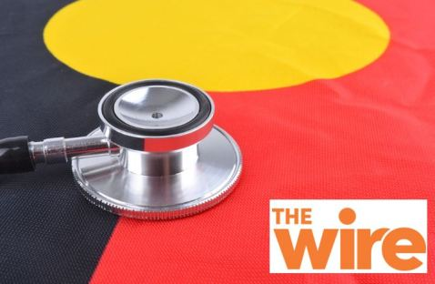 stethoscope on top of portion of Aboriginal flag & text 'The Wire' logo - orange text