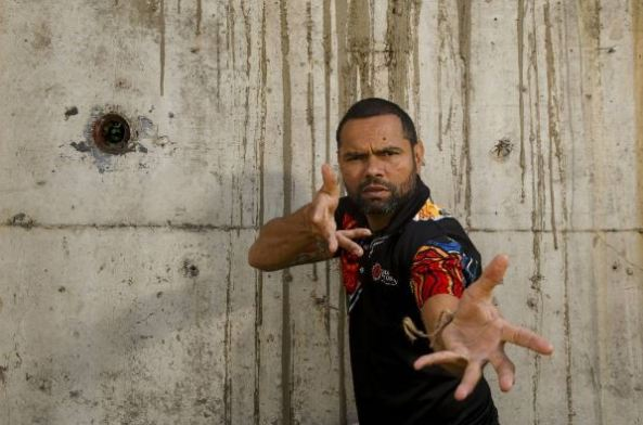 Illawarra Aboriginal health worker Dale Wright wearing shirt with Aboriginal art, against cement wall looking at camera with hands outstretched