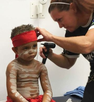 health professional checking ear of young Aboriginal boy with red band around head & white ochre across chest & red pants