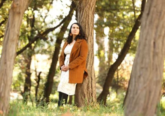 Garra Mundine with black boots, white dress & 3/4 length light brown coat leaning against a tree trunk in native woodland