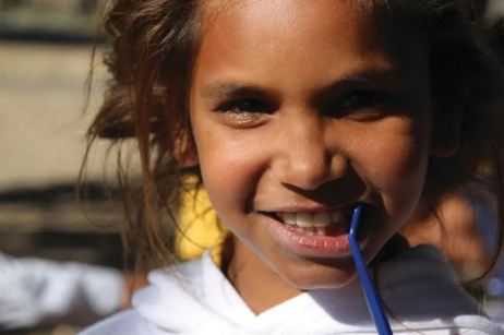 close up shot of face of young Aboriginal girl with a blue toothbrush in her mouth