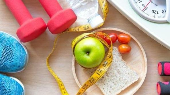 tip of sneakers, red hand weights, yellow tape measure, scales, apple, wholemeal bread slice, bottle of water & cherry tomatoes
