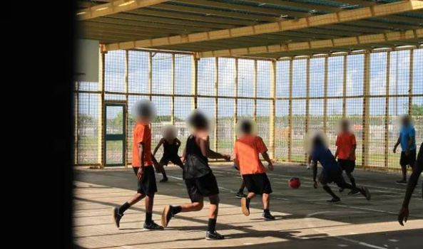 8 male youths playing basketball in Don Dale prison Darwin faces blurred