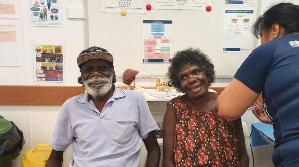 Aboriginal man & woman at the Miwatj Health Aboriginal Corporation, the woman is receiving the covid-19 vaccine by a health worker