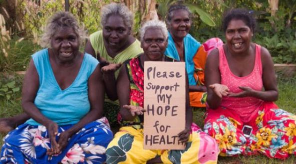 5 Aboriginal women sitting cross-legged in colourful tropical skirts, elder at front is holding a sign with words 'Please support my hope for health', tropical green foliage in background
