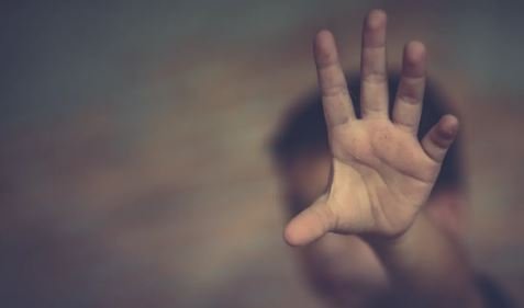 blurred image of youth with arm outstretched and palm facing camera obscuring face