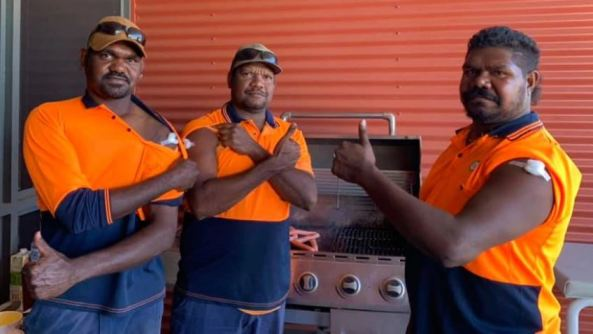 3 Aboriginal men in orange navy tradie polos with thumbs up showing cotton balls over vaccination site in upper arm