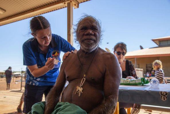 rremote area nurse administering a COVID-19 vaccine to a Balgo Aboriginal Elder WA, sitting at a table outside a building