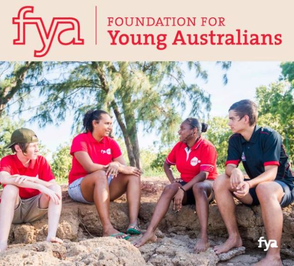 tile text 'FYA - Foundation for Young Australians' - photo of 4 participants on the IMPACT NT Indigenous Youth Leadership Program sitting outside on rocks, sandy soil, green trees in background